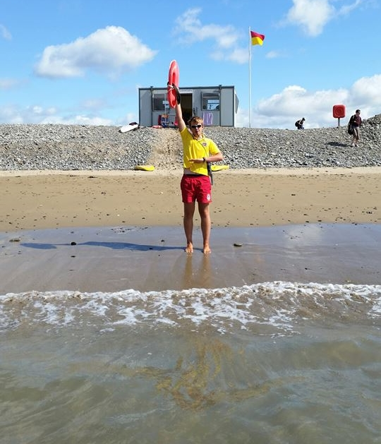 A Cork County Council Beach Lifeguard signalling a bather to come into and/or stay at waist depth.